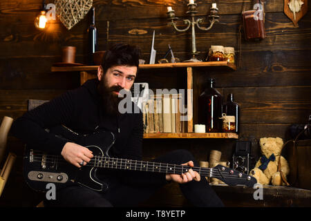 Favourite activity. Man bearded musician enjoy evening with bass guitar, wooden background. Guy in cozy warm atmosphere play relaxing soul music. Man - Stock Photo