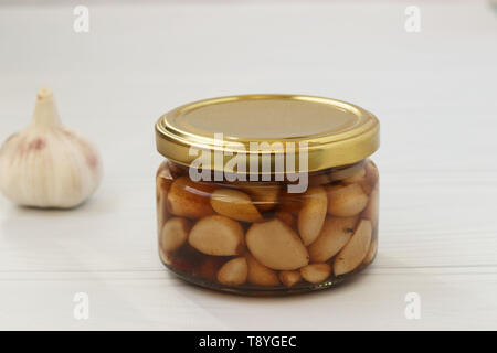 Marinated garlic in a jar on a white background - Stock Photo