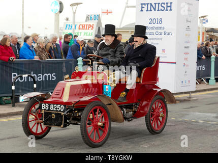 Mr Christopher Atkinson, driving his Maroon, 1903, De Dion Bouton, across the finish line, in Madeira Drive, at the end of the 2018 London to Brighton Veteran Car Run - Stock Photo