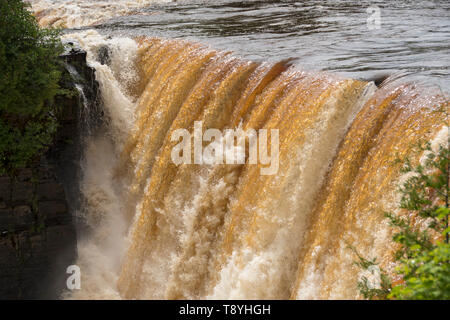 Cascading water over Kakabeka Falls, Ontario, Canada.  The colour of the water if due to tannin in the water from vegetation - Stock Photo