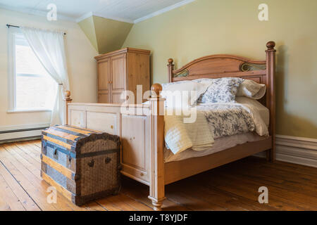 Queen size bed with wooden headboard and footboard, antique travel chest, armoire in upstairs master bedroom with oil stained fir wood floorboards inside an old 1900 Victorian Queen Anne revival style house, Quebec, Canada. This image is property released. CUPR0335 - Stock Photo