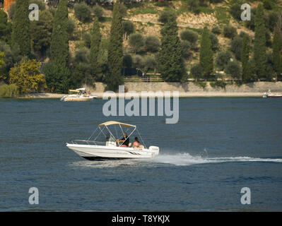LAKE GARDA, ITALY - SEPTEMBER 2018: Two people on a small boat with outboard motor on Lake Garda. - Stock Photo