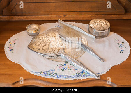 Silver antique beauty hand mirror, hair brush and comb on top of wooden dresser in upstairs guest bedroom inside an old 1927 American Four Squares house, Quebec, Canada. This image is property released. CUPR0221 - Stock Photo