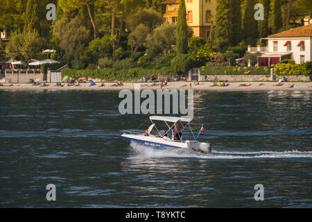 LAKE GARDA, ITALY - SEPTEMBER 2018: Two people on a small boat with outboard motor cruising on Lake Garda. - Stock Photo