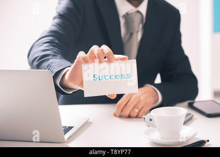 Businessman holding business card with success text written on it close up - Stock Photo