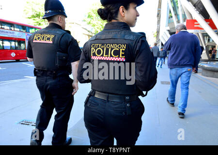 London, England, UK. Two City of London Police officers on patrol in Holborn - one male, one female - Stock Photo