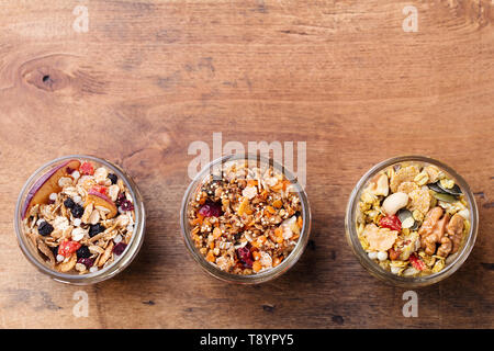 Assortment of granola, muesli in glass jars. Healthy breakfast. Oats with fruits, berries and nuts. Top view. Copy space - Stock Photo