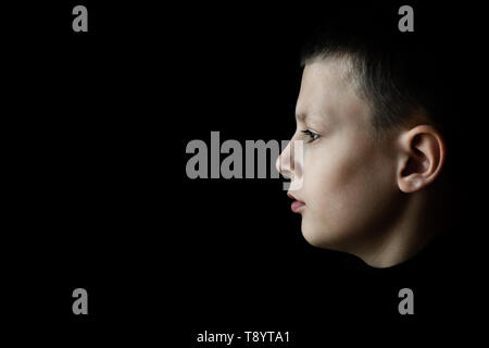 Depressed Sad Boy Profile Portrait on Black Background - Stock Photo