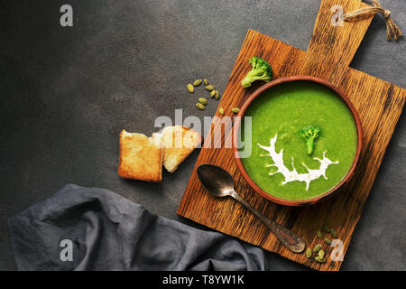 Green cream broccoli soup with sour cream and pumpkin seeds in a ceramic bowl on a cutting board, dark rustic background. Vegetarian lunch or dinner.  - Stock Photo