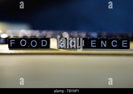 FOOD SCIENCE concept wooden blocks on the table. With personal development and motivation concept on blurred or black background - Stock Photo