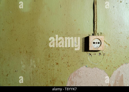 Old power socket isolated on damaged green wall - reconstruction background - Stock Photo