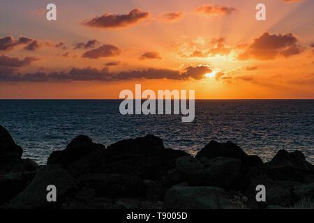 beautiful sunset in warm orange at the rocky coast of Playa Blanca, Lanzarote - Stock Photo