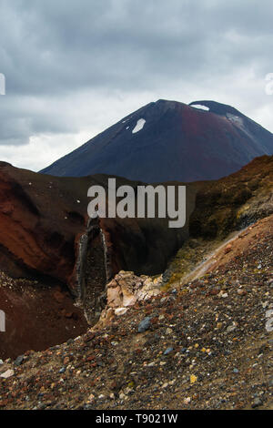 View of Mount Ngauruhoe - Mount Doom from Tongariro Alpine Crossing hike with clouds above and red crater in foreground. - Stock Photo