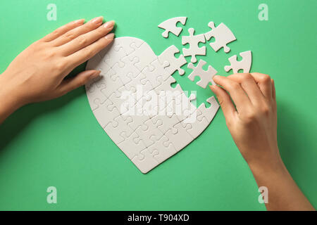 Woman doing jigsaw puzzle on color background - Stock Photo