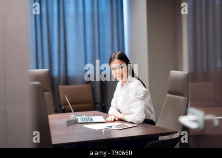 Beautiful young businesswoman using laptop in conference room - Stock Photo