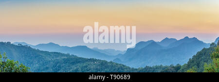 Nature Web Banner. Mountain view sunset panorama view of many hill and green forest cover with soft mist with colorful sky background, sunset at  Doi  - Stock Photo
