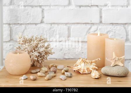 Seashells, pebbles and burning candles on table near white brick wall - Stock Photo