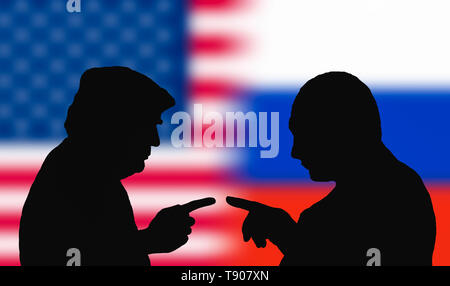 Silhouettes to represent the USA President, Donald Trump, and the Russian President, Vladimir Putin, facing each other pointing, as if arguing. - Stock Photo
