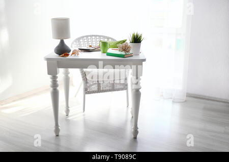 Beautiful coral with sea shells on white table in room - Stock Photo