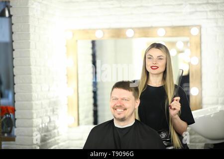 Girl Hairstylist and Man Customer in Beauty Studio - Stock Photo