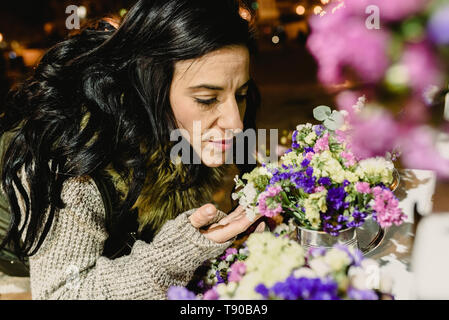 Brunette woman smelling flowers in a market at night. - Stock Photo