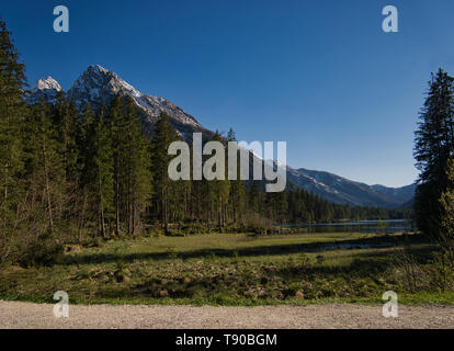 A gravel path on the shore of Hintersee in Berchtesgaden with forest and mountains - Stock Photo
