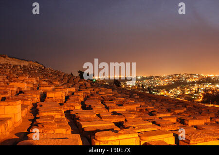 Jerusalem, Israel - March 03rd, 2015: Night view on the Jewish cemetery on Mount of Olives, lights of Jerusalem city in the background - Stock Photo