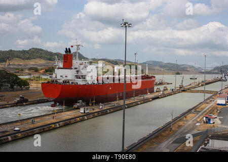Red tanker in ballast condition is passing through the Panama Canal at Miraflores Locks. It is going from the Pacific Ocean to the Caribbean Sea. - Stock Photo