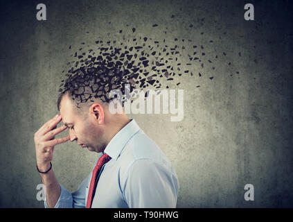 Memory loss due to dementia or brain damage. Side profile of a sad man losing parts of head as symbol of decreased mind function - Stock Photo
