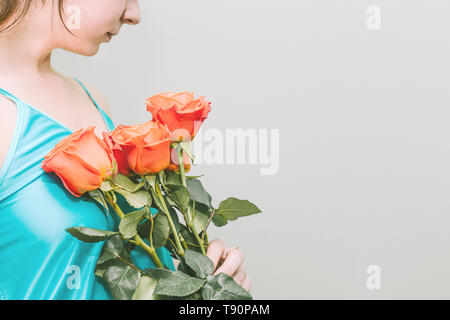 A young girl holds orange roses in her hands. A bouquet of bright flowers. On a beautiful girl wearing a turquoise shirt. Empty space for text - Stock Photo