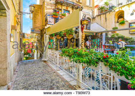 Restaurant workers prepare for the day at a colorful and picturesque cafe just off of Corso Umberto, the main street in Taormina Italy, Sicily - Stock Photo