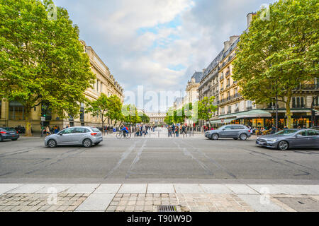 A street scene on the Ile de la Cite in the fourth arrondisement with the Palais du Justice visible on the right side of the pedestrian walkway - Stock Photo