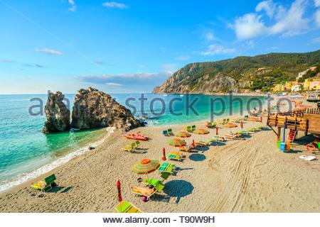 Chairs and umbrellas fill the Spiaggia di Fegina, the sandy beach in front of the village of Monterosso al Mare, Italy, part of the Cinque Terre - Stock Photo