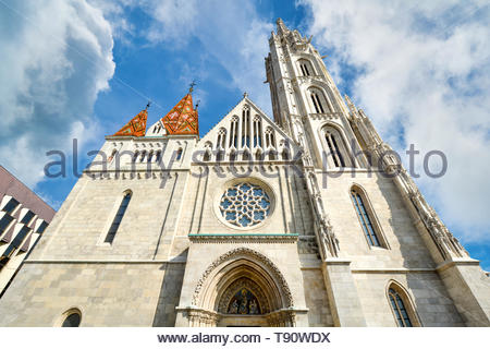 The front facade and rose window of Matthias Church at Buda's Castle Complex in Budapest Hungary on a sunny day - Stock Photo
