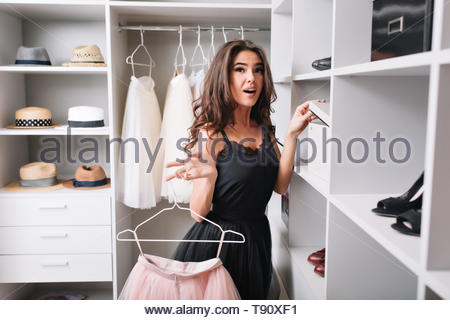 Pretty young woman with surprised look standing in nice wardrobe, interested what is inside box, holding pink fluffy skirt in hands. She's wearing black stylish dress. - Stock Photo