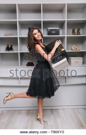 Attractive smiling girl bought new shoes, holding boxes in hands, standing in dressing room, wardrobe. She's looking to camera, one leg up. She wearing in black fluffy dress and silver high heels. - Stock Photo