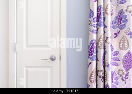 Home interior showing  colonial closet door with purple curtain decor and light blue painted wall. - Stock Photo
