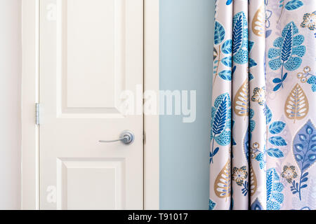 Home interior showing  colonial closet door with blue curtain decor and light blue painted wall. - Stock Photo