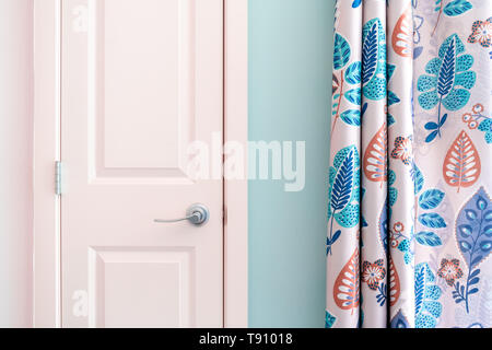 Home interior showing  colonial closet door with turquoise curtain decor and light blue painted wall. - Stock Photo