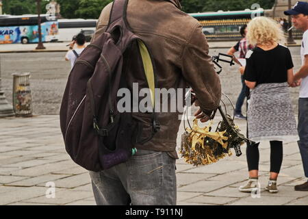 Illegal street vendor taking inventory of his merchandise while looking on at tourists - Stock Photo