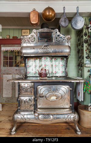 Antique 1915 Belanger Royal wood-burning cooking stove in kitchen with worn wide pinewood plank floorboards inside an old 1835 Canadiana cottage style house, Quebec, Canada. This image is property released. CUPR0347 - Stock Photo