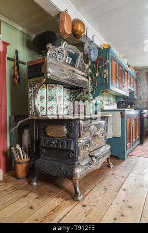 Antique 1915 Belanger Royal wood-burning cooking stove and pinewood with linden wood cabinets in kitchen with worn wide pinewood plank floorboards inside an old 1835 Canadiana cottage style house, Quebec, Canada. This image is property released. CUPR0347 - Stock Photo