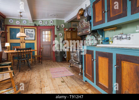 Pinewood with linden wood cabinets, antique 1915 Belanger Royal wood-burning cooking stove and dining table with assorted chairs in kitchen with worn wide pinewood plank floorboards inside an old 1835 Canadiana cottage style house, Quebec, Canada. This image is property released. CUPR0347 - Stock Photo
