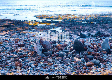 Small stones on a black beach, in the background are akean waves and a surfer - Stock Photo