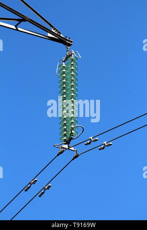 High quality tall glass power line utility insulators holding black electrical wires on strong metal utility pole on clear blue sky background - Stock Photo