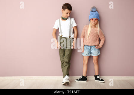 Cute boy and girl in fashionable clothes near color wall - Stock Photo