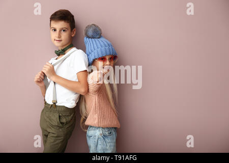 Cute boy and girl in fashionable clothes on color background - Stock Photo