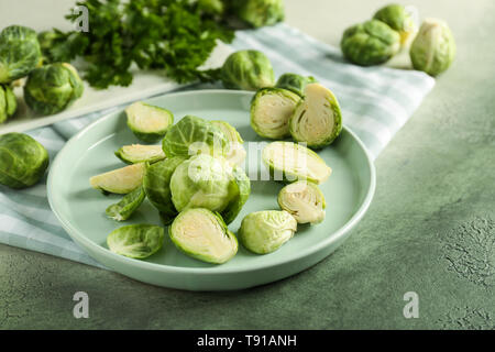 Plate with fresh brussels sprouts on table