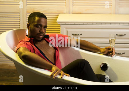 Macho with beard enjoy life with glass of champaign in luxury bathroom. Man on relaxed face relaxing in bathtub. Luxury life concept. Man with beard - Stock Photo