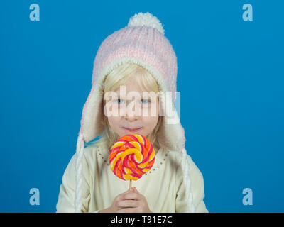 Snack on when you please. Little child with sweet lollipop. Little girl hold lollipop on stick. Happy candy girl. Happy childhood food - Stock Photo